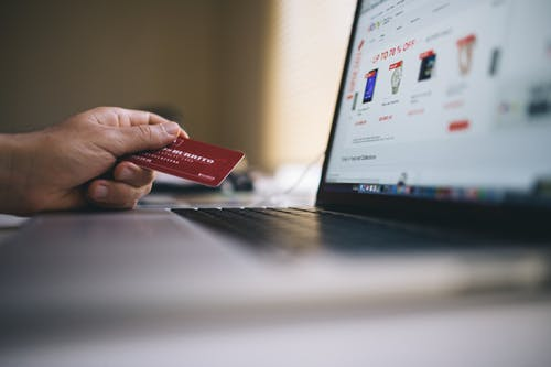 holding a credit card in front of a computer